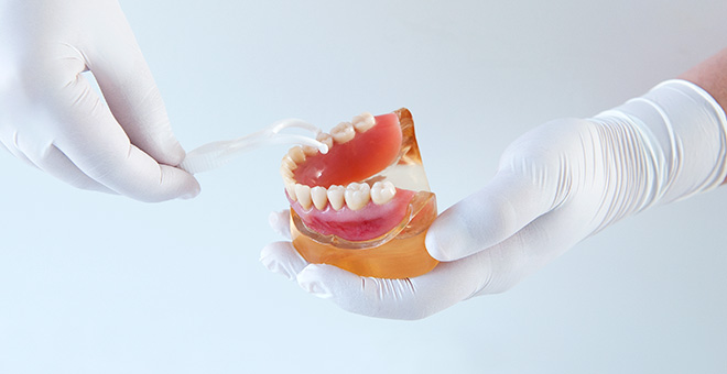 Gloved hands demonstrating with model of lower jaw for gum contouring purposes