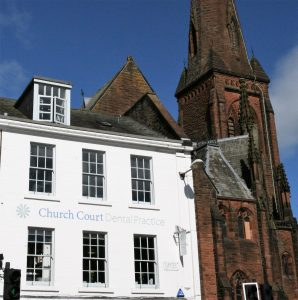 Church Court Dental Practice Dumfries with blue sky and Greyfriars Church